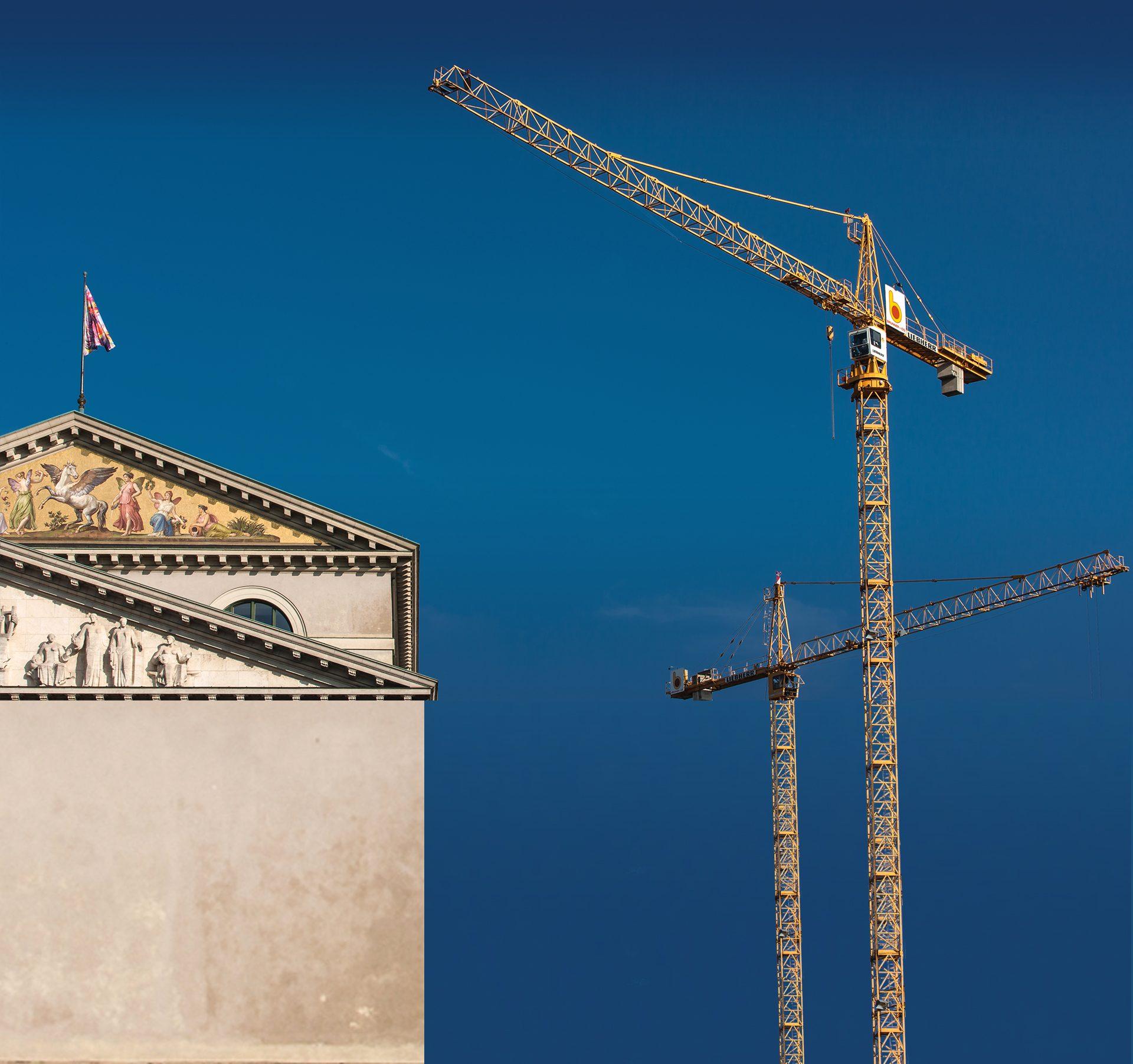 Zei Kräne rechts im Bild von BRUNNER + CO vor leuchtend blauem Himmel, links unten das Dach eines denkmalgeschützten Gebäudes