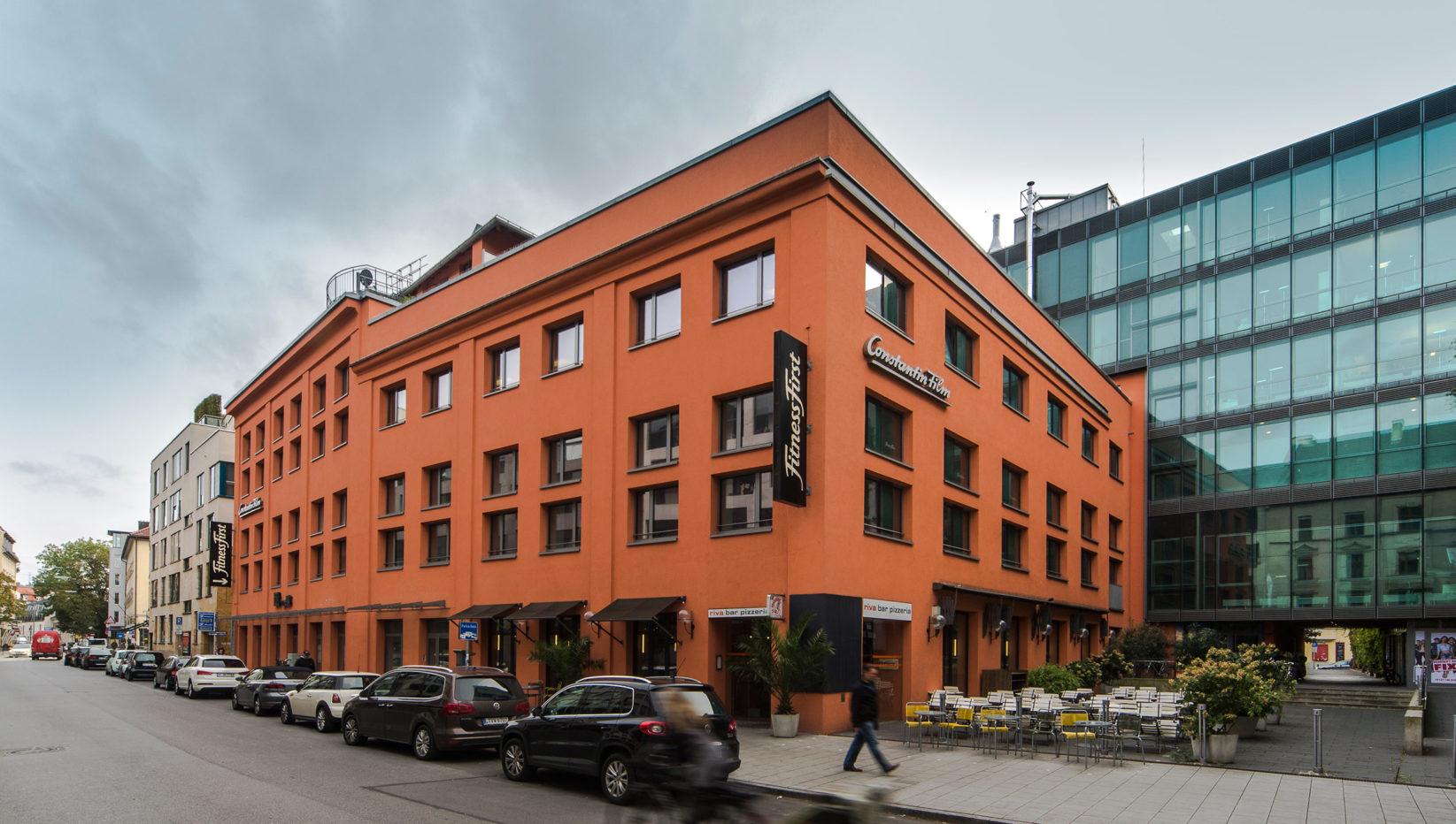 Ansicht der Factory Schabing von Nordosten von der Feilitzschstraße. Die rotbraune Fassade ist vorne zu sehen, dahinter ein Glasgebäude.
