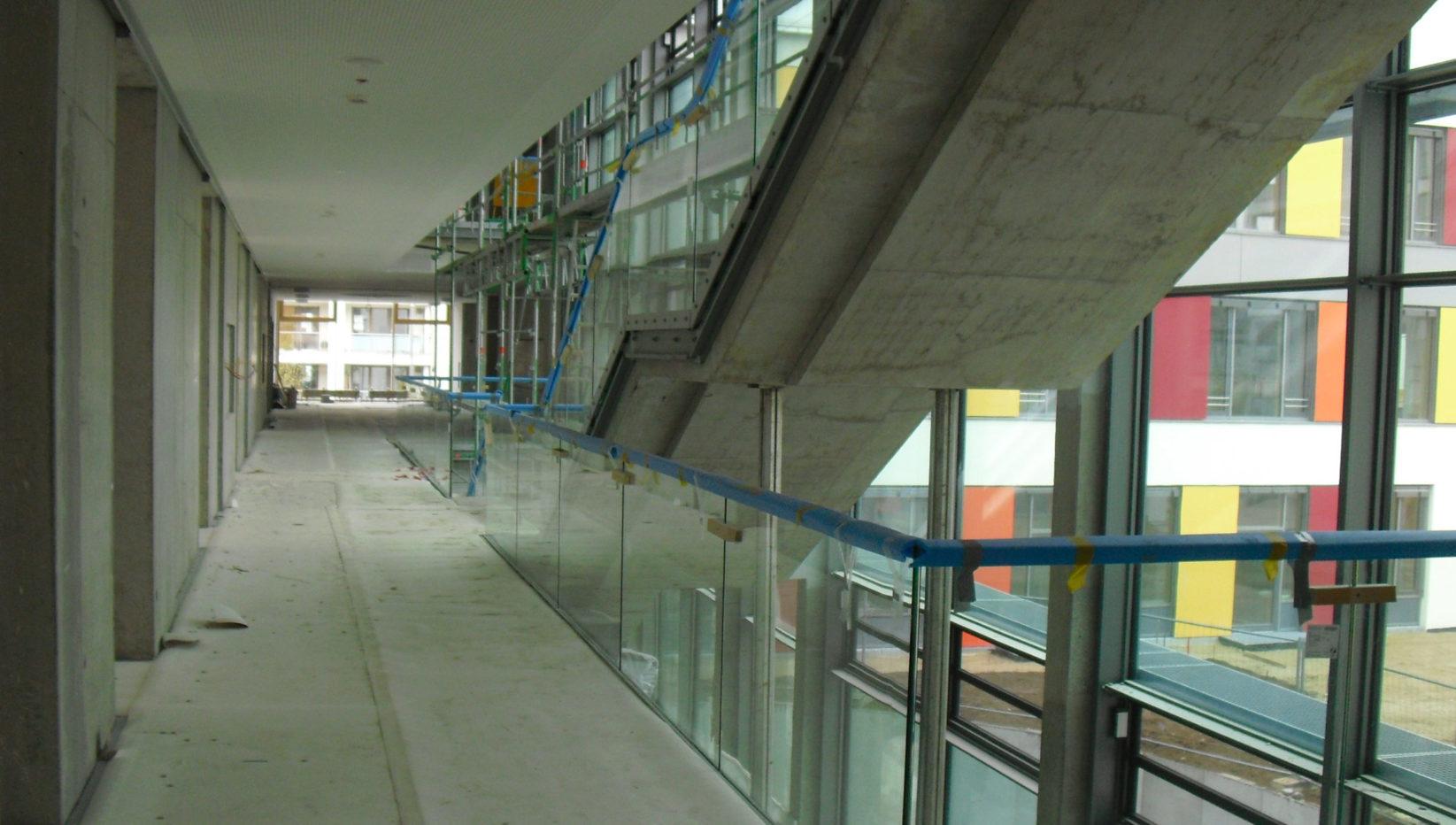 Innenaufnahme des Förderzentrums München Süd nach Fertigstellung des Rohbaus. Zu sehen ist der lange Flur und rechts die Treppe in das nächste Stockwerk aus Stahlbeton.