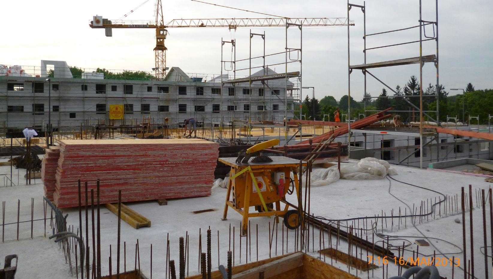 Aufnahme mit Blick auf Bauteil 40 des Rohbaus der Wohnanlage in München Harthof, davor stehen Baumaterialien und Baugerüste.