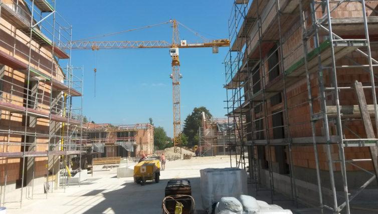 Im Vordergrund sieht man das Haus der Begegnung kurz vor der Fertigstellung der Rohbauarbeiten durch die Brunner + Co Baugesellschaft, im Hintergrund einen Baukran.