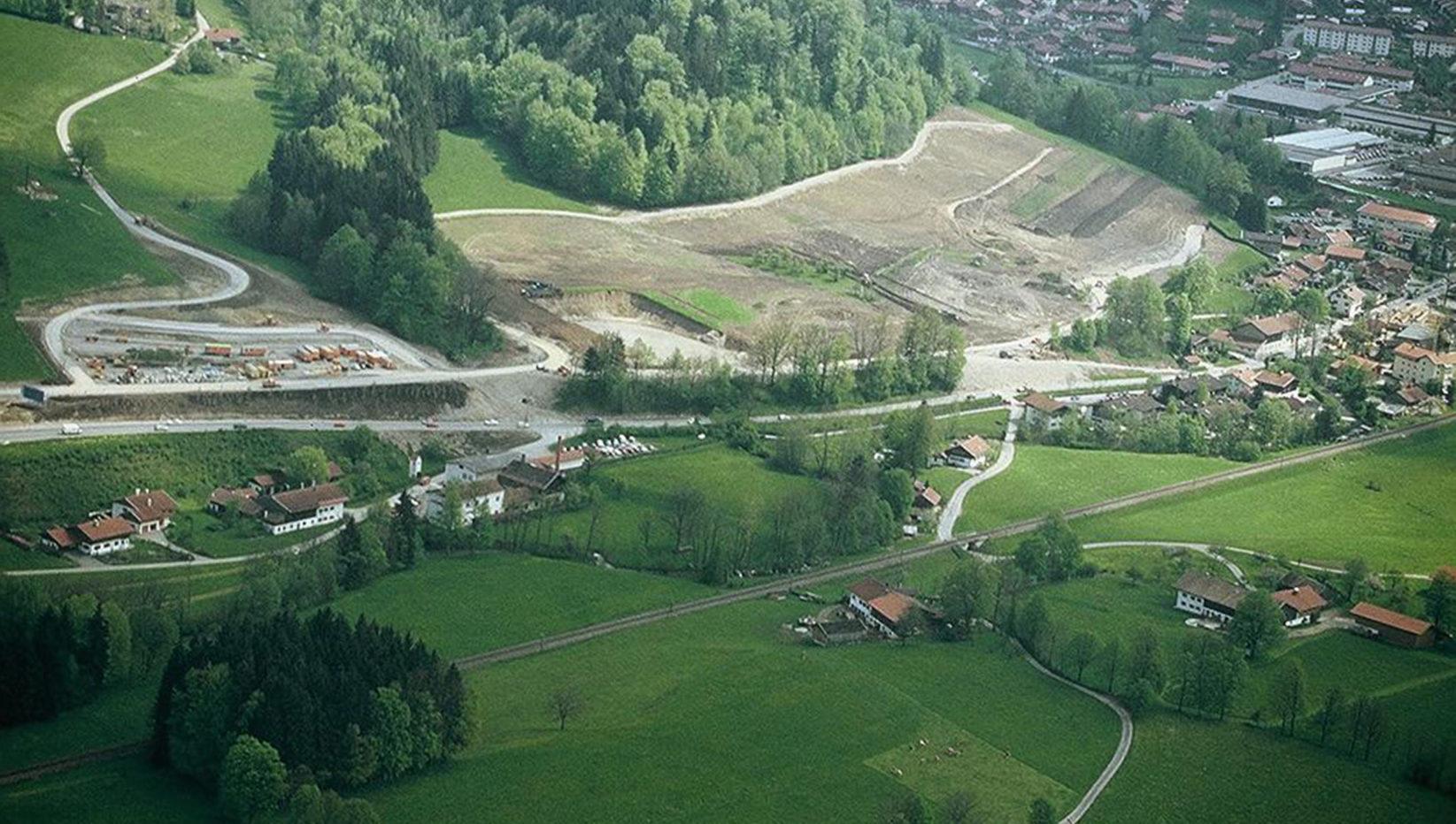 Luftaufnahme des Baugeländes vor Baubeginn des Kreiskrankenhauses Miesbach in Hausham. Drum herum sind Wiesen, Bäume und die Häuser der Ortschaft zu sehen.