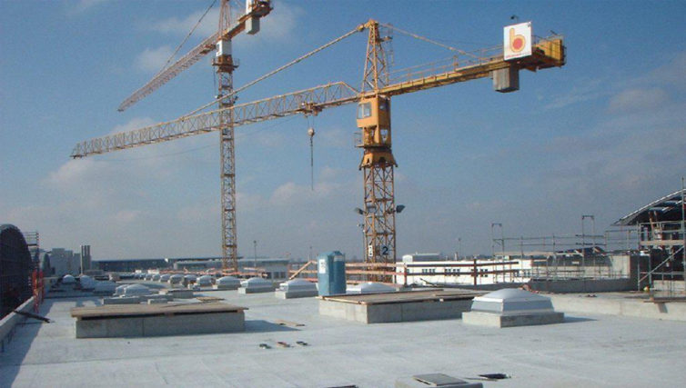 Aufnahme der Baugrube während des Rohbaus der Messehallen in Riem. Vorne Blick in die Baugrube mit Bauleitern, im Hintegrund Kräne beim Haupteingang Nord.