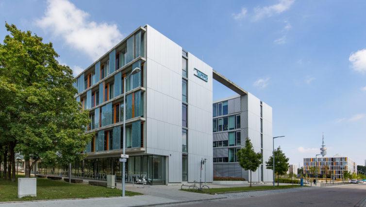 Zu sehen ist das Münchner Technologiezentrum von Außen in der Südostansicht. Das fünfstöckige Gebäude ist grau. Rechts unten führt eine Straße weg.