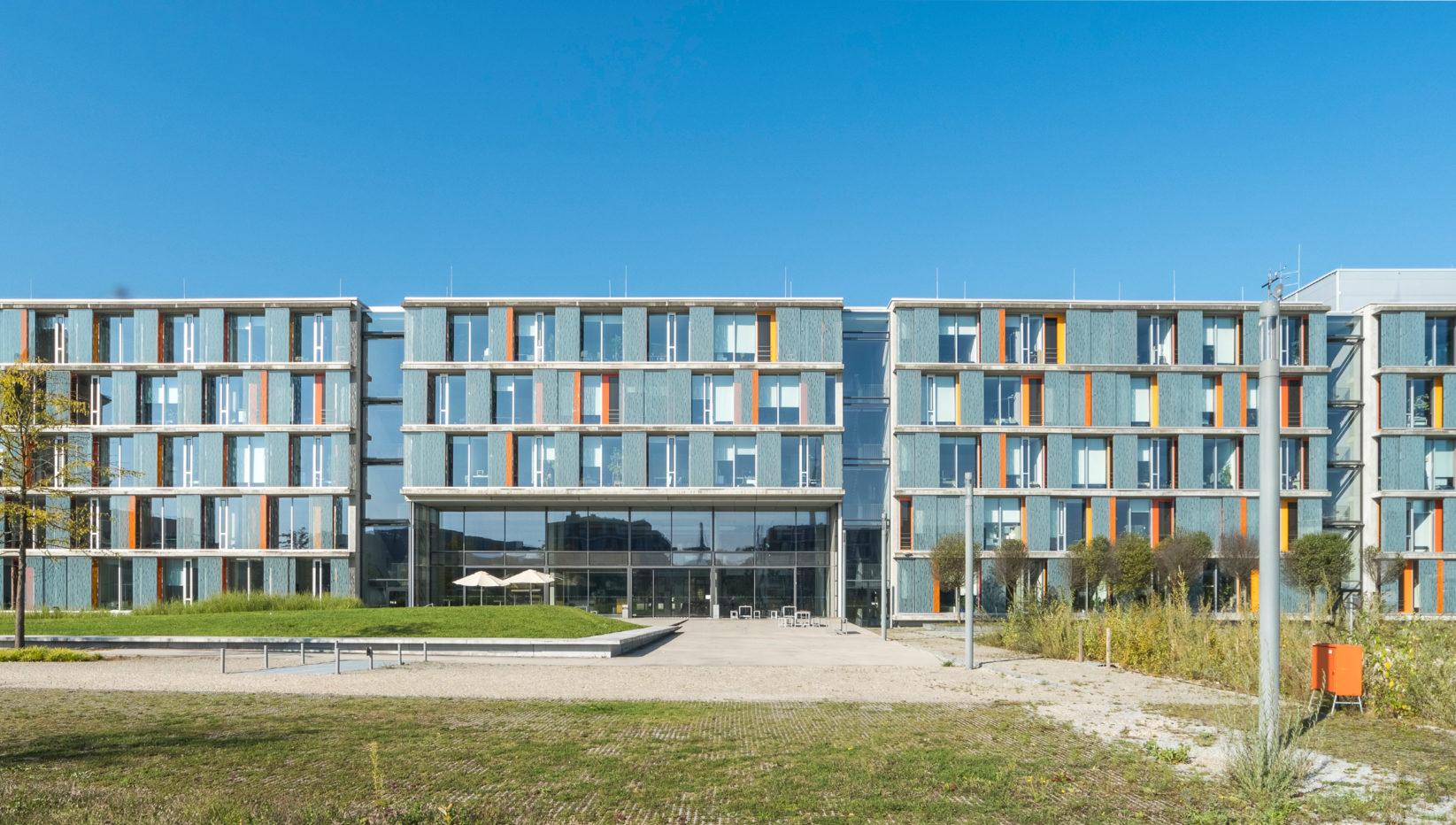 Darstellung des fünfstöckigen Münchner Technologiezentrums in der Frontalansicht. Zu sehen sind mehre Gebäude aus Sichtbeton mit verglaster Fensterfront.