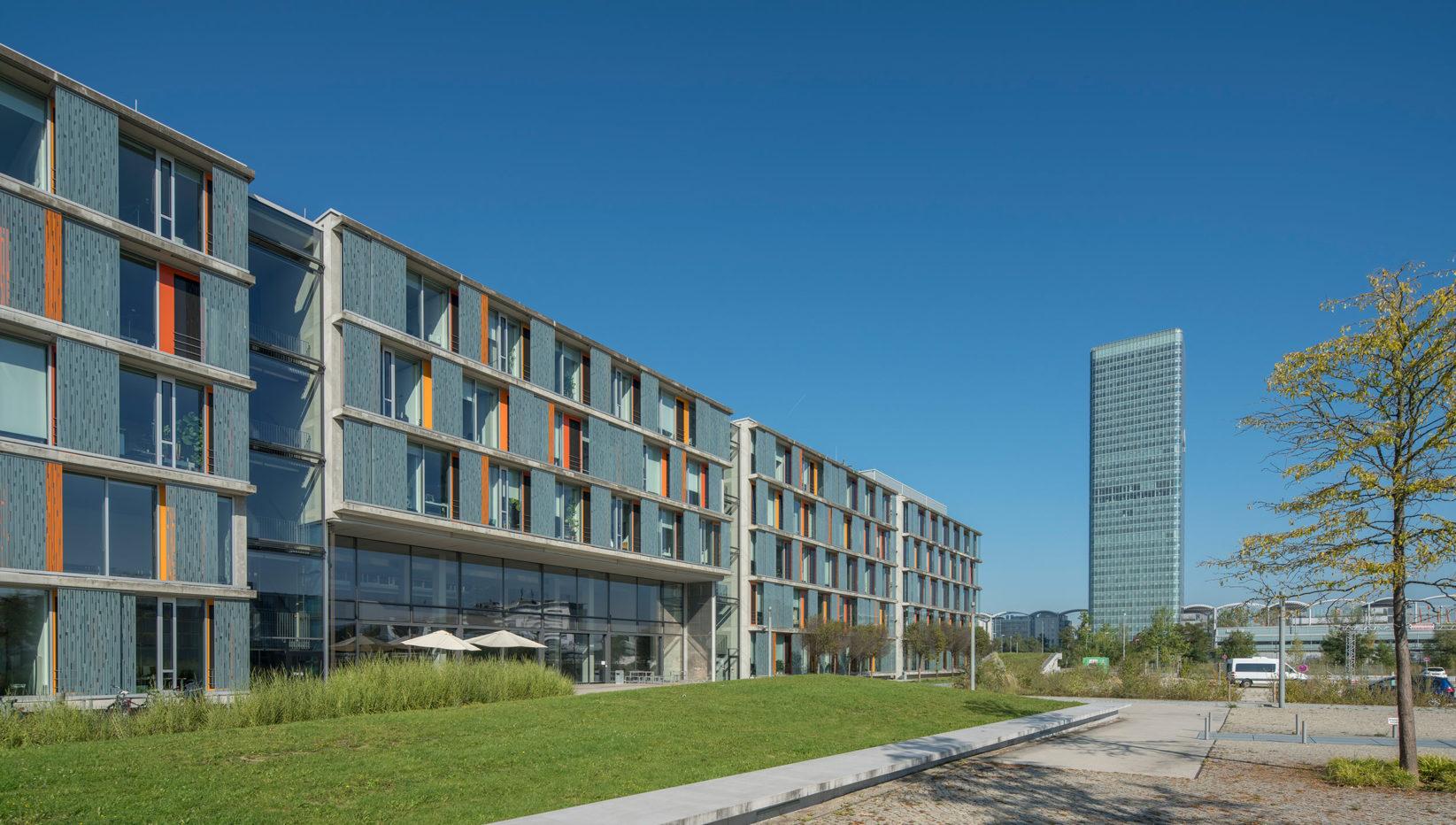 Die Südwestansicht bietet Blick auf das Forschungszentrum nach Fertigstellung der Rohbauarbeiten im steilen Fluchtwinkel. Rechts dahinter der O2 Tower von München.