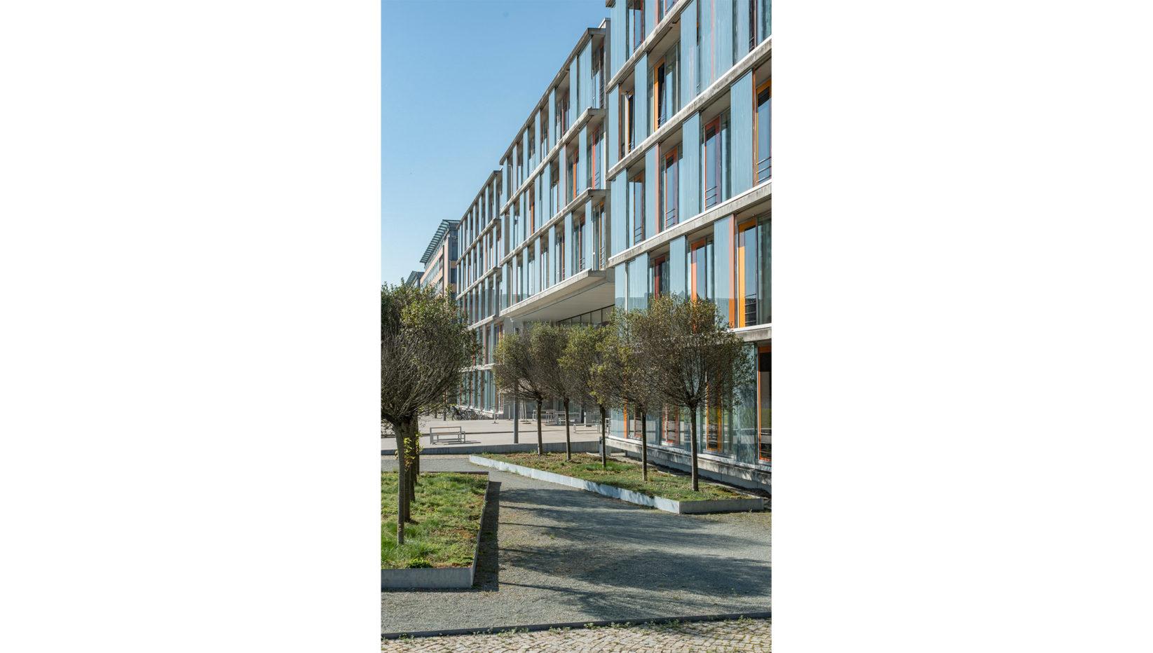 Nordwestansicht des Forschungszentrums München mit steilem Fluchtwinkel. Davor eine Anordnung von gepflanzten Bäumen vor dem Gebäude.