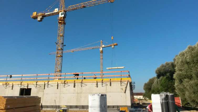 Zu sehen ist der Rohbau von Finger 1 der Realschule Freising in Stahlbetonbauweise, aufgenommen vom Boden. Dahinter stehen zwei Baukräne.