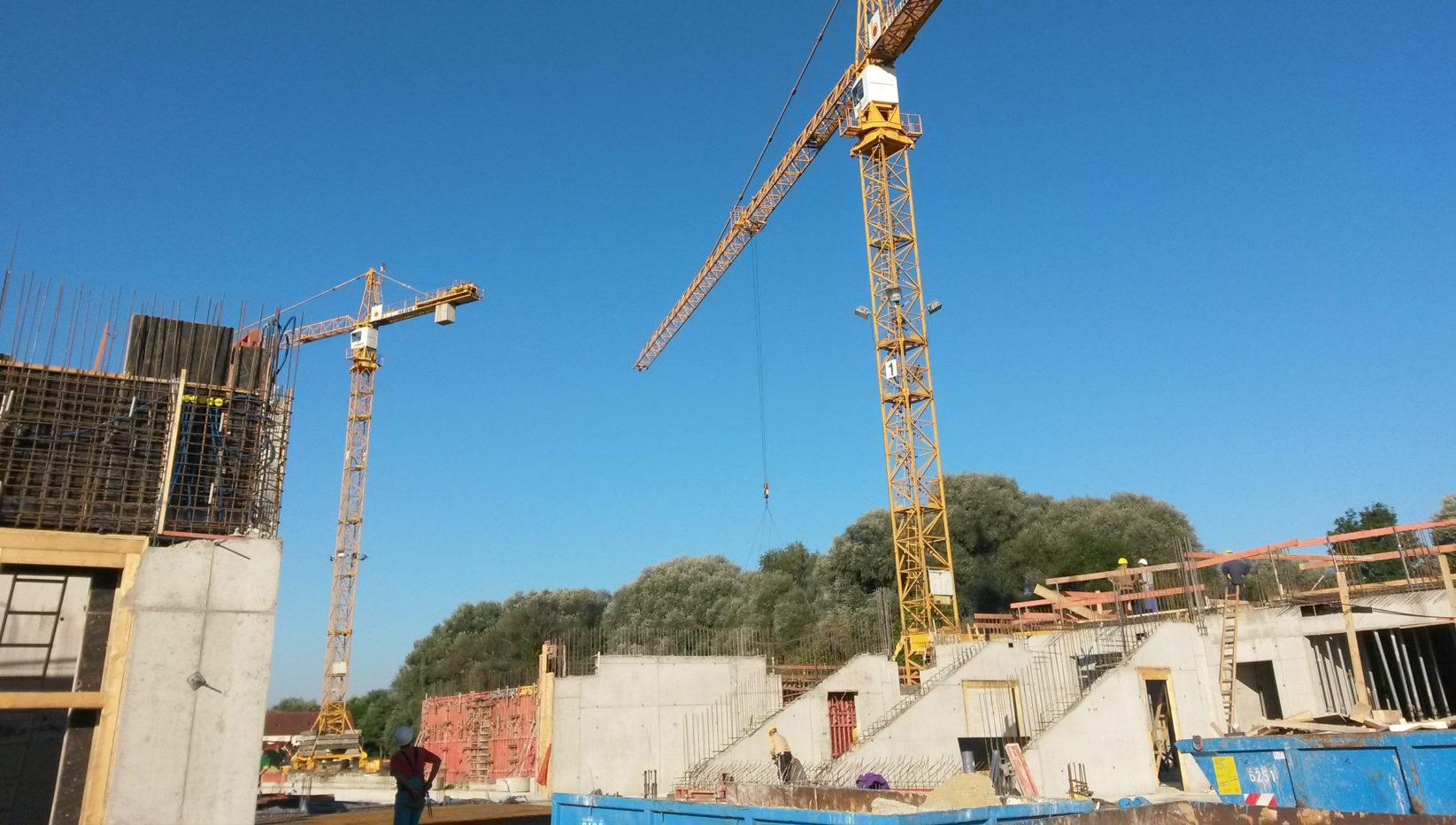Links dargestellt ist die Ecke des Schulgebäudes, rechts sieht man den Rohbau der Aula mit Tribüne. Dahinter zwei Baukräne und Bauleiter bei der Arbeit.