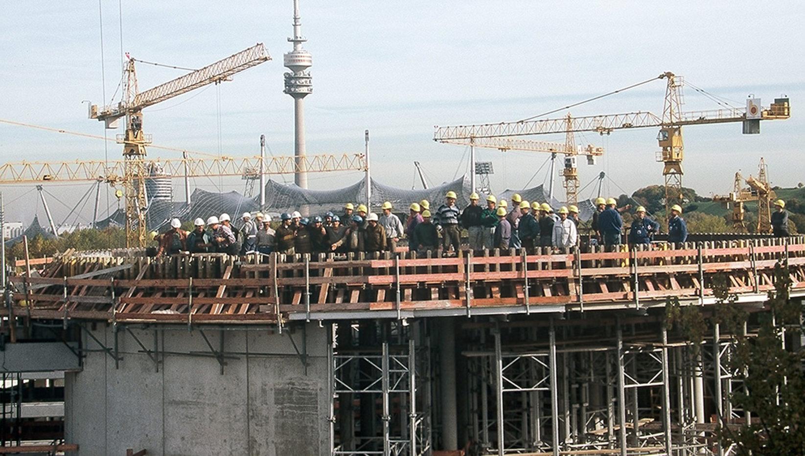 Aufnahme der Rohbauarbeiten für die Hauptverwaltung der Stadtwerke München, dahinter Baukräne und der Olympiaturm. Auf dem Bau steht die Belegschaft von Brunner + Co.