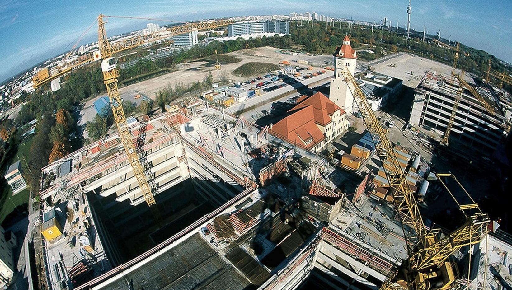 Luftaufnahme des Bürozentrums für die Verwaltung der Stadtwerke München kurz vor Fertigstellung der Betonarbeiten. Zu sehen sind 6-stöckige Gebäude und Kräne.