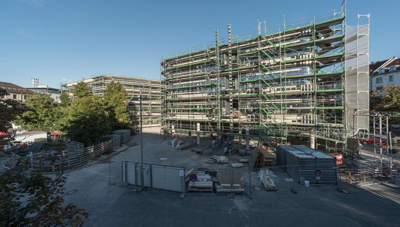 Aufnahme des Rohbaus des TranslaTUM aus der Ostansicht, eingehüllt in Baugerüste. Davor liegen Baumaterialien auf der Baustelle.