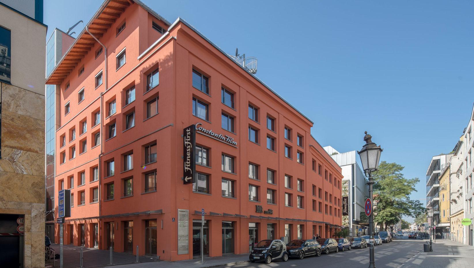 Zu sehen ist das 6 geschossige Gebäude der Factory Schwabing in einem rotbraunem Farbton. Aufgenommen wurde es in Nordwestansicht von der Feilitzschstraße aus.