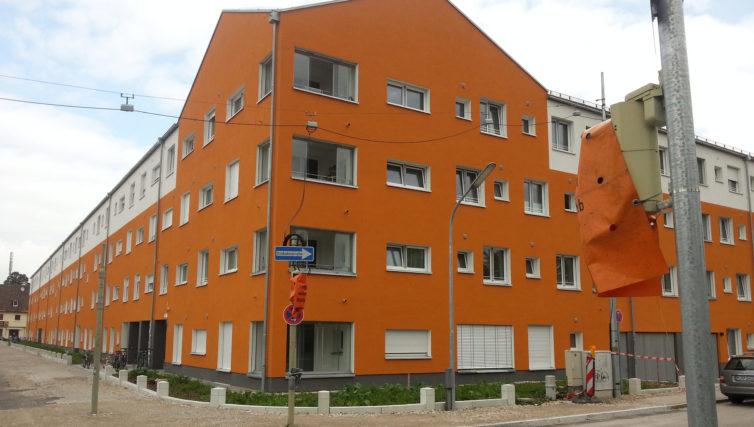 Südostansicht der Wohnanlage in München Harthof nach Fertigstellung durch Brunner + CO. Die Fassade des fünfstöckigen Gebäudes ist orangebraun gestrichen.