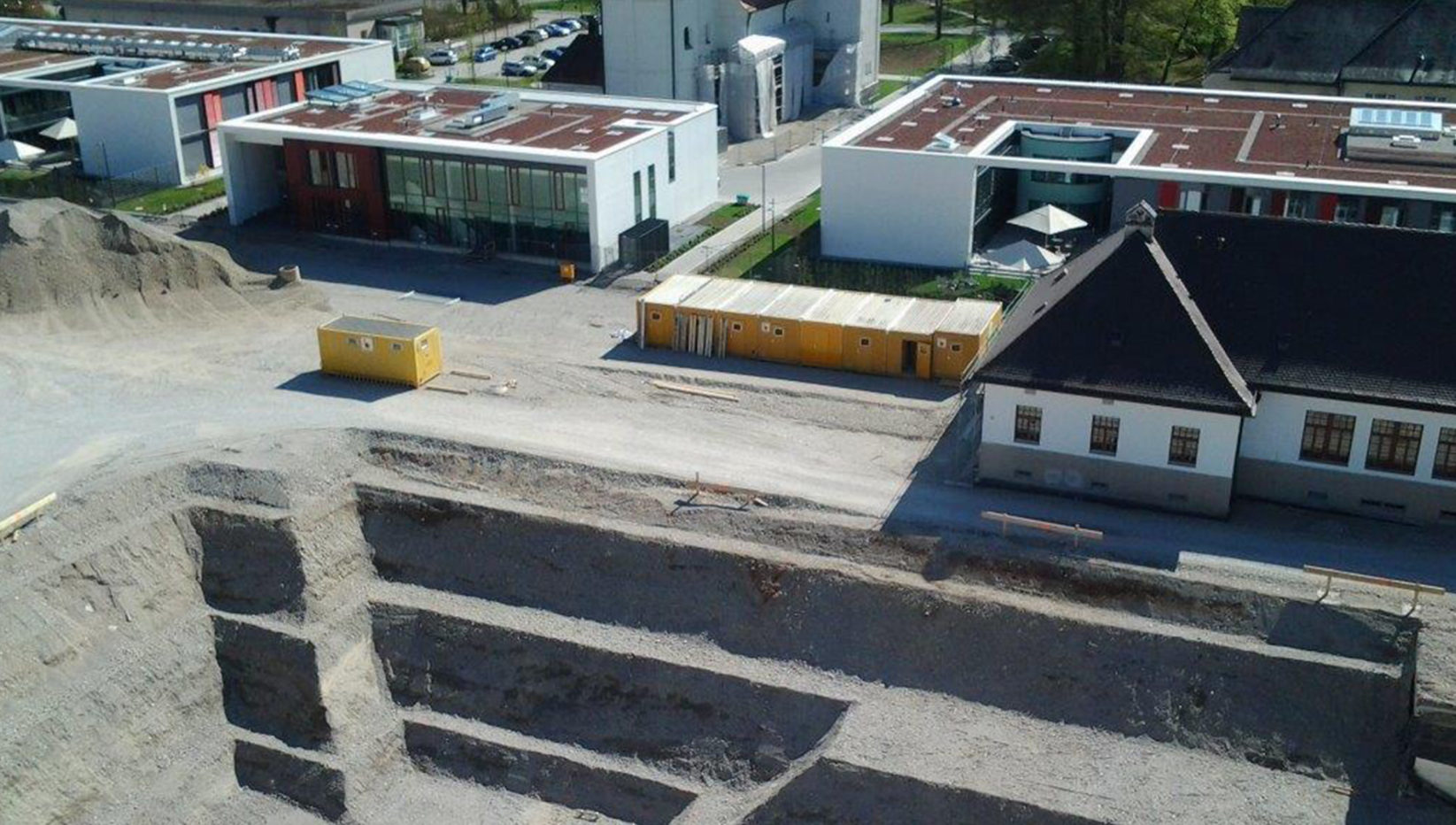 Luftaufnahme der Baugrube in München Haar. Am unteren Bildrand sieht man die Baugrube für die Psychiatrie, darüber einige bestehenden Gebäude mit Flachdach.