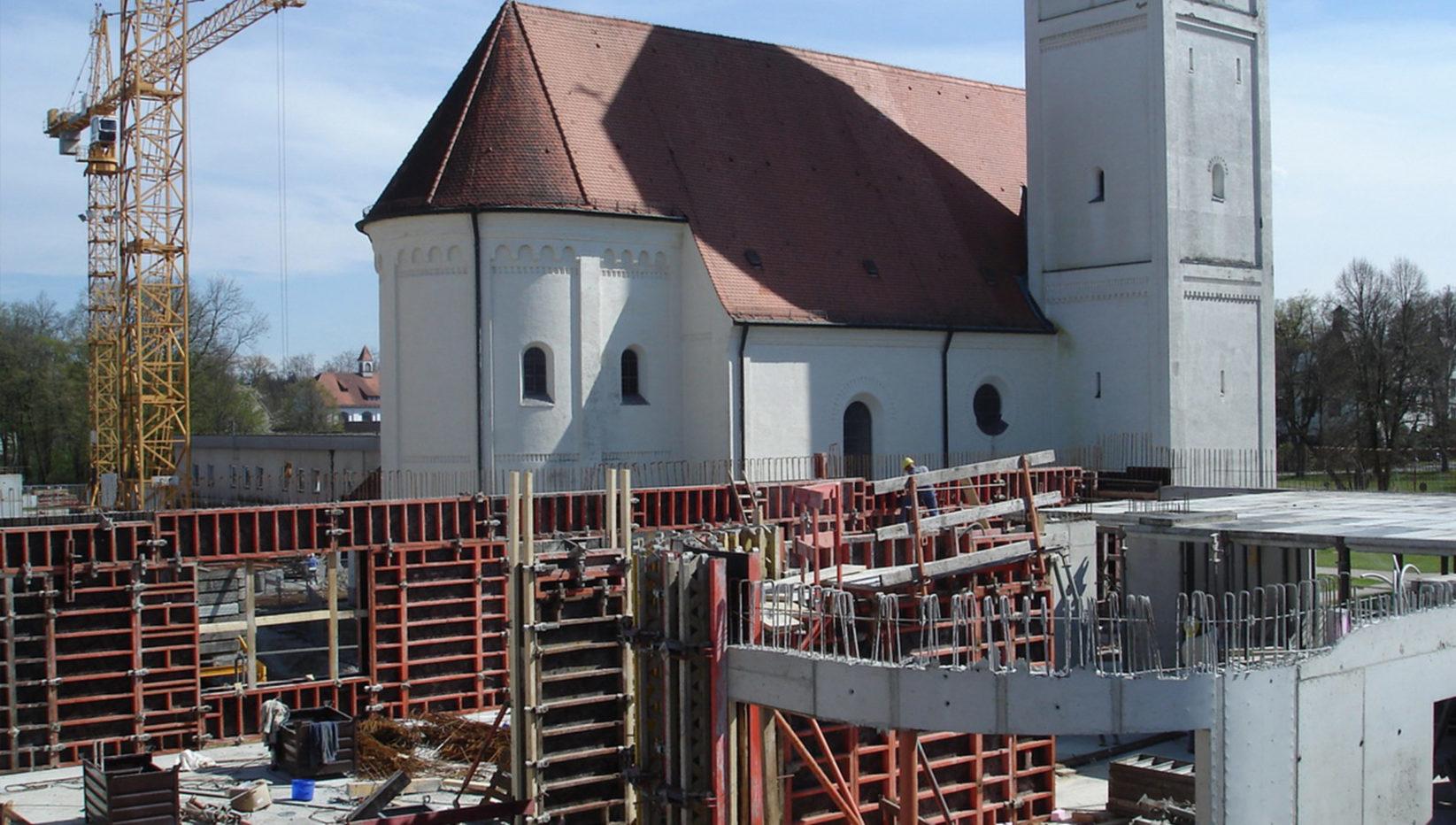 Vorne im Bild ist der Rohbau der Psychiatrie in München zu sehen, dahinter links ein Kran der Brunner + Co Baugesellschaft mbH und rechts eine Kirche mit rotem Dach.