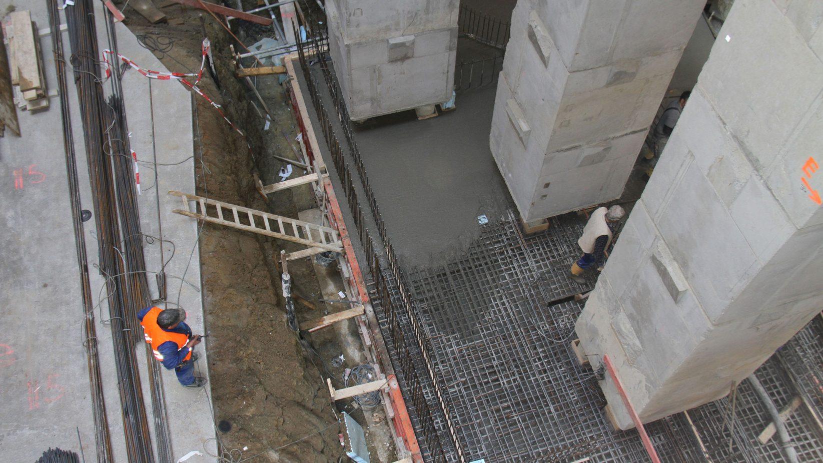 Abbildung der Arbeiten am Großbauprojekt in der Maximilianstraße. Aufnahme der Baugrube von oben, Betonbalken rechts und ein prüfender Bauleiter links im Bild.