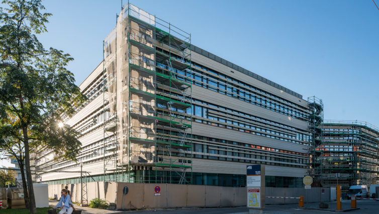 Foto des TranslaTUM in München aus der Südwestansicht nach den Rohbauarbeiten. An der Ecke des Gebäudes sind Baugerüste zu sehen.